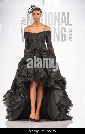 ExCel London, London, 14th April 2018. An unusual black dress shown by a model on the catwalk. The National Wedding Show takes place at ExCel London Exhibition Centre this weekend, showcasing the latest bridal trends, accessories, dresses and everything around planning the perfect wedding. Credit: Imageplotter News and Sports/Alamy Live News - Stock Photo