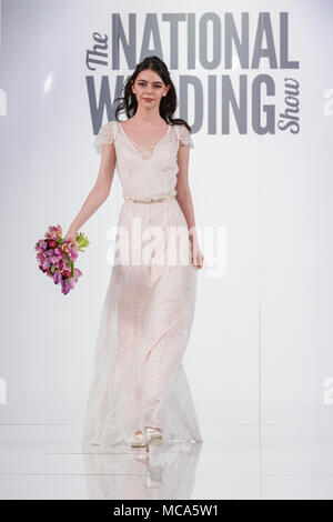ExCel London, London, 14th April 2018.  A model shows an intricate wedding dress on the catwalk. The National Wedding Show takes place at ExCel London Exhibition Centre this weekend, showcasing the latest bridal trends, accessories, dresses and everything around planning the perfect wedding. Credit: Imageplotter News and Sports/Alamy Live News - Stock Photo