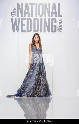 ExCel London, London, 14th April 2018. A model shows a beautiful wedding dess on the catwalk.The National Wedding Show takes place at ExCel London Exhibition Centre this weekend, showcasing the latest bridal trends, accessories, dresses and everything around planning the perfect wedding. Credit: Imageplotter News and Sports/Alamy Live News - Stock Photo