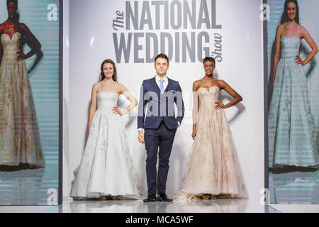 ExCel London, London, 14th April 2018. Models showswedding desses and suits on the catwalk.The National Wedding Show takes place at ExCel London Exhibition Centre this weekend, showcasing the latest bridal trends, accessories, dresses and everything around planning the perfect wedding. Credit: Imageplotter News and Sports/Alamy Live News - Stock Photo