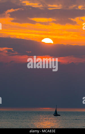 Aberystwyth Wales UK, Saturday 14 April 2018  UK Weather:  A yacht sails on the calm sea as the sun sets over Cardigan Bay,  off  the ciast at Aberystwyth Wales at the end of a warm spring day, with more warm weather forecast for the UK in the coming week   photo © Keith Morris / Alamy Live News - Stock Photo