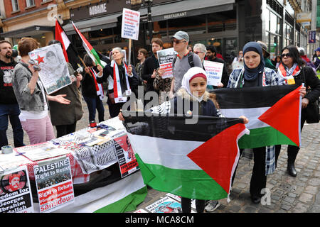 London, UK 14th April 2018   Muslim girl and her mother holding Palestinian flags at a Palestinian rights demo opposite the Israeli embassy in Kensington, London, United Kingdom.  The slightly raucous demonstration was reasonably well supported with around 60 people in attendance.  It was called to protest about the continuing tension in the Gaza strip following recent violence between the two sides.  London, UK 14th April 2018   gathering of five pro-Israel protestors heckled the demonstration from the other side of the road. Credit: Michael Preston/Alamy Live News - Stock Photo