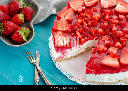 Homemade creamy dessert cake pie of red strawberry fresh fruit on blue wooden background with knife and fork - Stock Photo