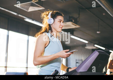 Theme sport and music. A beautiful Caucasian woman running in gym on treadmill. On head big white headphones, the girl listens to music during a cardio workout for weight loss and uses phone in hand - Stock Photo