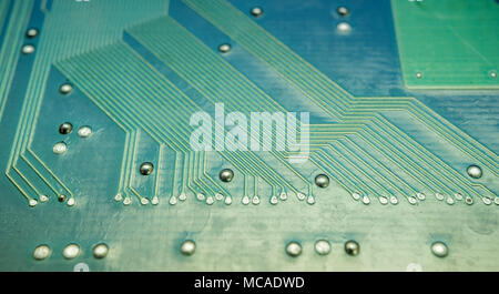 Fine traces and solder joints on computer board, micro engineering - Stock Photo