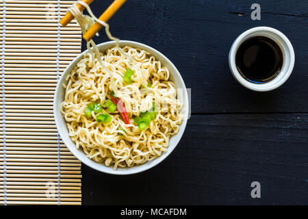 Bowl of instant cooked plain noodles with chopsticks and pepper garnish - Top view photo - Stock Photo