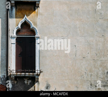 Looking up at an old stucco window frame bathed in light, with white window frames  in Venice, Italy. - Stock Photo