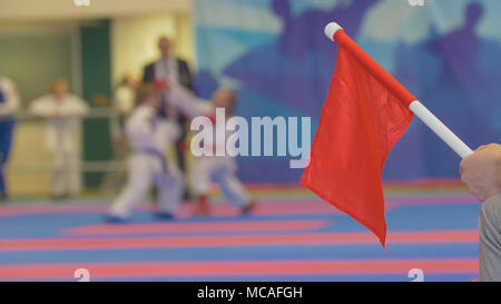 Red flag in front of teenager girls fighting at the karate tournament - Stock Photo