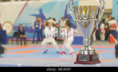 Teenager girls fighting in kimono at all in front of silver cup - Stock Photo