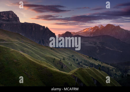 View on illuminated Marmolada highest peak in Dolomites from Sella pass at sunrise. - Stock Photo