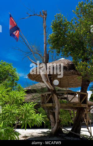 Wooden beach house on the tree with radio receiver. Cambodian flag on the top. Koh Rong Samloem, Cambodia. - Stock Photo
