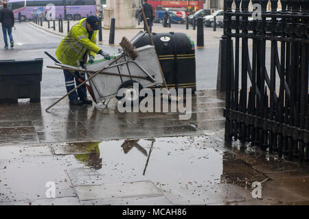 A street sweeper emptying a bin is reflected in a puddle on a rainy London street - Stock Photo