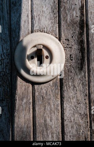 old electric light switch on a wooden wall - Stock Photo