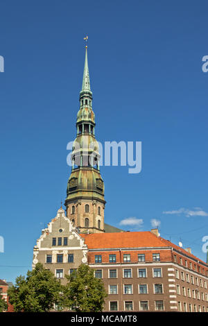 Saint Peter`s church tower above facades of historical house and apartment building on a sunny day with clear blue sky - Stock Photo