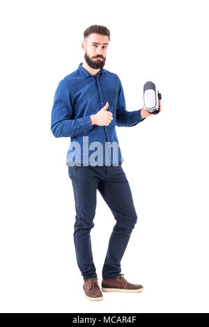 Satisfied business man holding vr headset with admiration thumb up gesture looking at camera. Full body isolated on white background. - Stock Photo