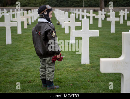 180203-N-YO638-118 EPINAL, France (Feb. 3, 2018) Aaron Howson, a French citizen, helps place luminaries upon the graves of fallen American service members at the Epinal American Cemetery. Howson comes to the cemetery every Sunday to lower the American flag during taps and pay tribute to the fallen service members. (DoD photo by Mass Communication Specialist 3rd Class Cody Hendrix/Released) - Stock Photo