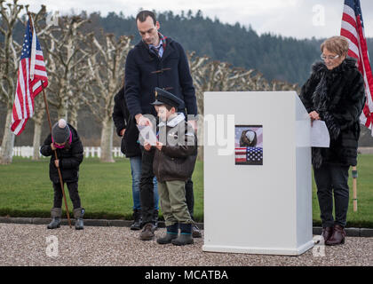 180203-N-YO638-278 EPINAL, FRANCE (Feb. 3, 2018) Aaron Howson, a French citizen, reads a poem dedicated to American service members during a remembrance ceremony at Epinal American Cemetery. More than 5,000 luminaries were placed on the graves of fallen American service members during the event. (DoD photo by Mass Communication Specialist 3rd Class Cody Hendrix/Released) - Stock Photo