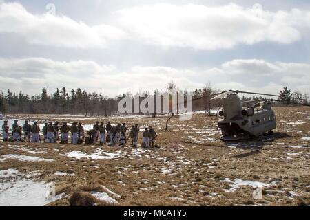 Soldiers line up ready to board a CH-47 Chinook helicopter from B Company, 3-10 General Support Aviation Battalion, 10th Combat Aviation Brigade, 10th Mountain Division, during a cold load training on air assaults at Fort Drum, New York, on February 2. The air assault operation lasted six days, with Aviators training and executing the air movement with three companies of Soldiers from 2nd Battalion, 87th Infantry Regiment, 2nd Brigade Combat Team, 10th -Mountain Division (LI). (U.S. Army photo by Spc. Thomas Scaggs) 170202-A-TZ475-195 - Stock Photo