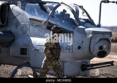 A Royal Marines Commando walks toward a Bell AH-1Z Viper at a Forward Arming and Refueling Point at Marine Corps Air Ground Combat Center, Twentynine Palms, Calif., Feb. 4, 2018, as a part of Integrated Training Exercise 2-18. The purpose of ITX is to create a challenging, realistic training environment that produces combat-ready forces capable of operating as an integrated MAGTF. (U.S. Marine Corps Photo by Pfc. William Chockey) - Stock Photo
