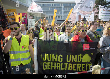 Potsdam, Germany. 15th April, 2018. Members of the German United Services Trade Union Verdi protest outside the conference hotel shortly before the beginning of the third negotiation round in the labour dispute for the public service. They carry a banner which reads 'Jung und gehaltbereit' (lit. young and ready for salary). So far the employers denied the union's demands for six percent more wage but at least 200 euros.  federation. Photo: Ralf Hirschberger/dpa Credit: dpa picture alliance/Alamy Live News - Stock Photo