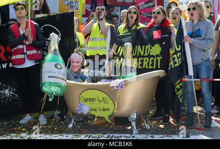 Potsdam, Germany. 15th April, 2018. Members of the German United Services Trade Union Verdi protest outside the conference hotel shortly before the beginning of the third negotiation round in the labour dispute for the public service. One of the participants of the protests wears a mask of German Minister of the Interior Seehofer and sits inside a plastic bath tub with the lettering 'Champagner fuer alle' (lit. champagne for everyone). So far the employers denied the union's demands for six percent more wage but at least 200 euros. Credit: dpa picture alliance/Alamy Live News - Stock Photo