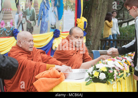 London UK. 15th April 2018. Buddhist monks offer blessings as members of the British Thai community celebrate   the Thai New Year (Songkran) at the Buddhapadipa Temple in Wimbledon, the largest Thai temple in the UK with religious ceremonies Thai classical music and dancing performances as well as stalls selling Thai food, groceries and souvenirs Credit: amer ghazzal/Alamy Live News - Stock Photo