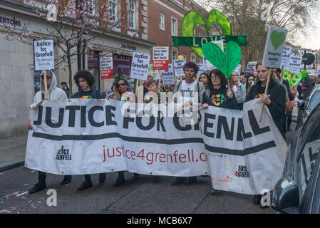 London, UK. 14th Apr, 2018. People including many who lost family and friends at Grenfell march with the Justice for Grenfell banner in a silent walk marking 10 months since the disaster. They met at Kensington Town Hall to stress that they hold Kensington and Chelsea Council responsible for the tragedy and for failing to deal effectively with is aftermath, with many survivors still not properly rehoused. Credit: Peter Marshall/Alamy Live News - Stock Photo