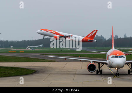 Stansted Airport, Essex, 15th April 2018  Aircraft movements at a foggy Stansted Airport in Essex, UK G-ezup Easyjet Airbus A320-214 takes off past another Easyjet on the taxi way Credit: Ian Davidson/Alamy Live News - Stock Photo