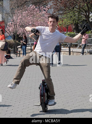 An Englishman living in New York riding an electric unicycle in Union Square Park in Manhattan, New York City. - Stock Photo