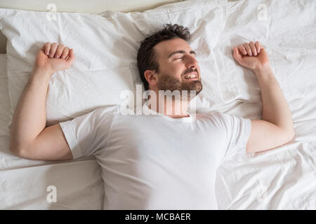 Top view of handsome man smiling while sleeping in his bed at home - Stock Photo