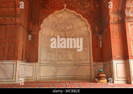 Muslim praying in Jama Masjid mosque in Delhi, India - Stock Photo