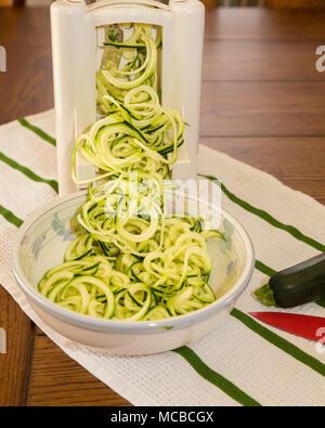 Spiral zucchini noodles called zoodles prepared in spiralizer kitchen gadget - Stock Photo