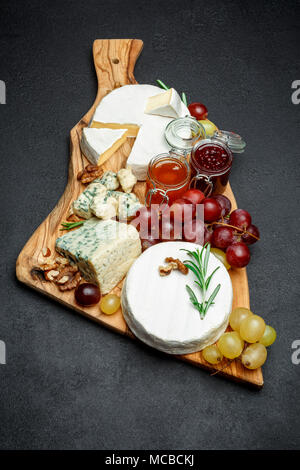 various types of cheese and jam on wooden cutting board - Stock Photo