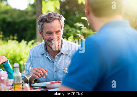 Portrait of a man in a group of friends gathered around a table in a garden on a summer evening to share a meal and have a good time together. - Stock Photo