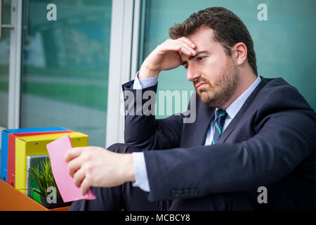 Sad manager after reading downsize notice pink slip - Stock Photo