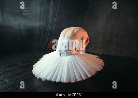 Ballet dancer sitting on stage, back view - Stock Photo