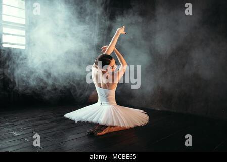 Female classical ballet performer sitting on floor - Stock Photo