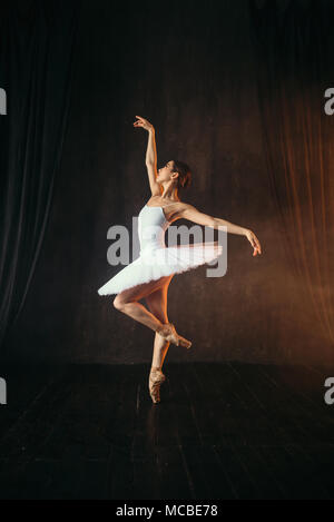 Ballerina in white dress and pointe shoes dancing - Stock Photo