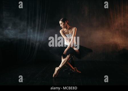 Ballet dancer sitting on black banquette - Stock Photo