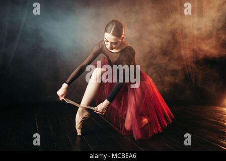 Ballet dancer tying pointe shoes - Stock Photo