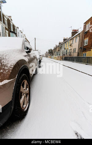 England, Ramsgate. Snow covered side street early morning after snowfall, with parked car on side in foreground, close-up. - Stock Photo