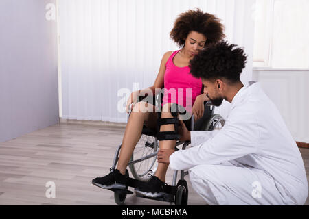Young Male Physiotherapist Fixing Knee Braces On Woman's Leg In Clinic