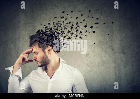 Memory loss due to dementia or brain damage. Side profile of a man losing parts of head as symbol of decreased mind function. - Stock Photo