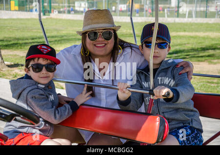 A mother and her young family sit on a quadracycle and pose for a family photograph. - Stock Photo