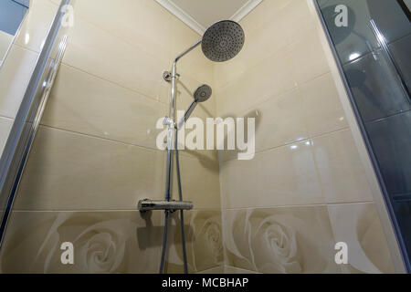 Close up of interior of new luxurious modern shower cabin with light beige ceramic tiling on walls. - Stock Photo
