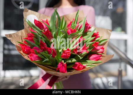 bouquet of beautiful flowers in women's hands. Floristry concept. Spring colors. the work of the florist at a flower shop. Horizontal photo - Stock Photo