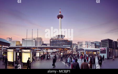 Kyoto Station busy with people in the evening with Kyoto tower and Kyoto tower hotel beautiful sunset city scenery in - Stock Photo