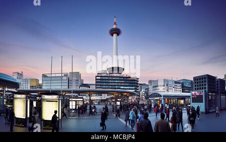 View on Kyoto tower from Kyoto Station busy with people in the evening, beautiful sunset city scenery in Shimogyo-ku, Kyoto - Stock Photo