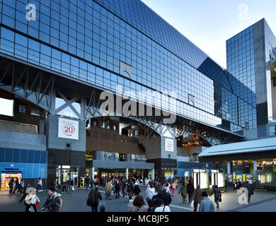 Kyoto Station, Kyoto-eki, modern glass building busy with people in the evening, second largest train station building in Japan. - Stock Photo