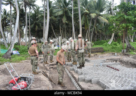 BIGEJ, Marshall Islands (March 20th 2018) Seabees assigned to Naval Mobile Construction Battalion (NMCB) 11, Construction Civic Action Detail Marshall Islands discuss project progress with leadership from the United States Army Garrison, Kwajalein Atoll. NMCB-11 is forward deployed to execute construction, humanitarian and foreign assistance, and theater security cooperation in the 7th Fleet area of operations. - Stock Photo